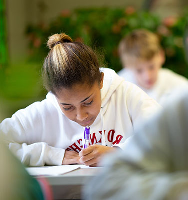 A student sits and works on an assignment in the classroom.