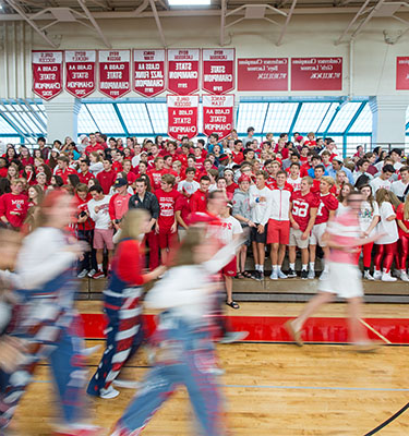 Students run through gymnasium during a pep fest.