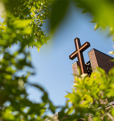 View of the large cross on top of the bet36体育在线 chapel, peering through a sunny tree.