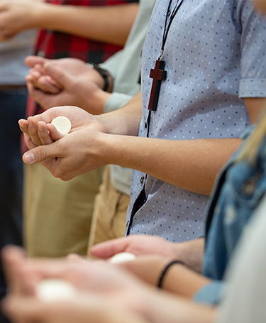 students taking communion at mass