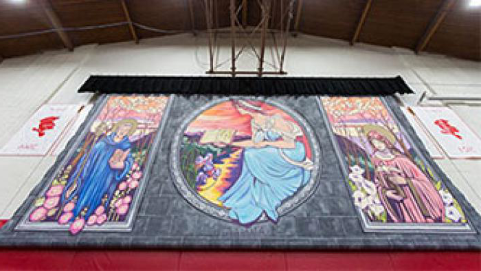 An upward view of the floor to ceiling col要么ful mural of saints hanging in the gym.